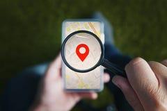 Tir des mains masculines tenant la loupe avec l'icône rouge du Geo-emplacement et regardant par elle au smartphone photographie stock libre de droits