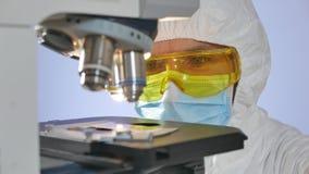 Tir en gros plan d'un microbiologiste regardant une plaque en verre avec des bactéries se préparant à l'examen sous le microsc banque de vidéos