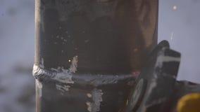 Tir en gros plan d'une cannelure de travailleur coutures de soudure sur un tuyau d'acier extérieur en hiver clips vidéos