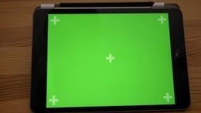 Tir en gros plan de approche de comprimé horizontal avec l'écran vert sur le fond en bois de bureau banque de vidéos