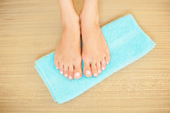 Tir en gros plan de beaux pieds de femme avec les clous roses lumineux sur la serviette bleue Photographie stock