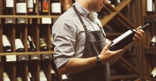 Tir en gros plan de bouteille de participation de sommelier de vin rouge dans la cave photographie stock libre de droits