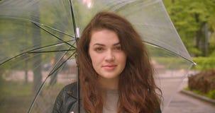 Tir en gros plan de brune caucasienne femelle sous des montres de parapluie dans la caméra avec le sourire calme en parc vert de  banque de vidéos