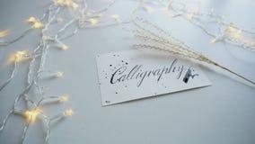 Tir en gros plan de carte postale avec la calligraphie italique de lettrage sur la feuille de papier blanche parmi la guirlande s banque de vidéos