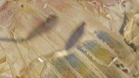 Tir en gros plan de l'image abstraite moderne de peinture de la main de l'artiste masculin avec la peinture et la spatule arcryli banque de vidéos