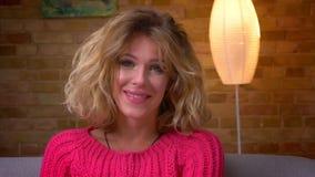 Tir en gros plan de la jolie femme au foyer aux cheveux ondulés dans le chandail rose souriant joyeux dans la caméra en atmosphèr banque de vidéos
