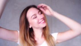 Tir en gros plan de portrait de fille de danse avec le beau sourire sur le fond du mur léger dans la chambre de jour banque de vidéos