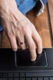 Tir en gros plan de trackpad émouvant de main du ` s des hommes sur l'ordinateur portable Images stock