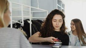 Tir en gros plan des clients féminins payant des vêtements au bureau du ` s de caissier dans la boutique d'habillement La jeune f banque de vidéos