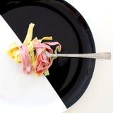Tir en gros plan des gens avec les pâtes savoureuses de PF de 3 couleurs Image libre de droits