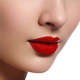 Tir en gros plan des lèvres de femme avec le rouge à lèvres rouge brillant Maquillage rouge de lèvres de charme, peau de pureté R Photos libres de droits