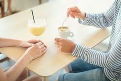 Tir en gros plan des mains de femake avec des boissons sur la table au café Image stock