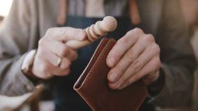 Tir en gros plan des mains masculines professionnelles d'artisan polissant le portefeuille en cuir fait main avec le bâton en boi banque de vidéos