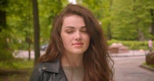 Tir en gros plan des montres femelles de brune caucasienne dans la caméra avec le sourire calme en parc vert de ville banque de vidéos