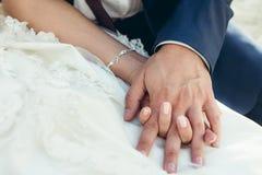 Tir en gros plan des nouveaux mariés tenant tendrement des mains Photos libres de droits
