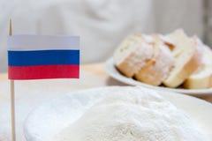 Tir en gros plan du drapeau et de la farine russes dans un plat Tranches de pain sur le fond Photos libres de droits