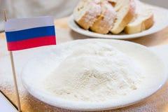 Tir en gros plan du drapeau et de la farine russes dans un plat Tranches de pain sur le fond Images libres de droits