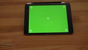 Tir en gros plan lentement de approche de comprimé horizontal avec l'écran vert sur le fond en bois de bureau banque de vidéos