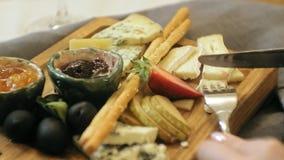 Tir en gros plan : plateau délicieux de fromage avec des sauces, des fruits et des baies banque de vidéos