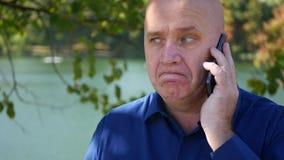 Tir extérieur avec un homme faisant un appel téléphonique sur l'allée de parc banque de vidéos