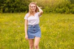Tir ext?rieur de T-shirt de jolie femme blonde et de jupe occasionnels blancs de port de denim, posant dans le pr?, touchant ses  images stock