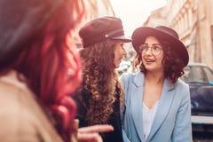 Tir extérieur de trois jeunes femmes élégantes parlant sur la rue de ville Amis riant et ayant l'amusement Photos libres de droits
