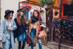 Tir extérieur de trois jeunes femmes marchant sur la rue de ville Amis parlant et ayant l'amusement Photos libres de droits