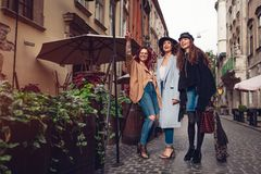 Tir extérieur de trois jeunes femmes marchant sur la rue de ville Filles examinant la distance Photos stock