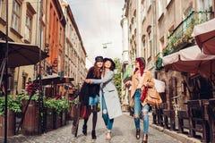 Tir extérieur de trois jeunes femmes marchant sur la rue de ville Filles parlant et étreignant Photographie stock libre de droits