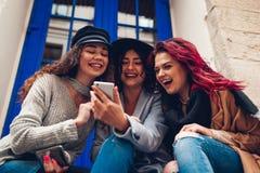Tir extérieur de trois jeunes femmes regardant le smartphone et riant par le café Filles parlant et ayant l'amusement Photo stock