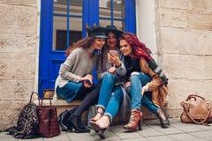 Tir extérieur de trois jeunes femmes regardant le smartphone et riant sur la rue de ville Filles parlant et ayant l'amusement Image libre de droits