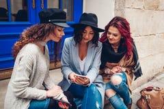 Tir extérieur de trois jeunes femmes regardant le smartphone sur la rue Filles parlant et ayant l'amusement Photo libre de droits