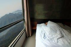 Tir grand-angulaire de jeune homme beau dormant confortablement dans le lit avec la belle vue de matin de nature de montagne des  Image libre de droits