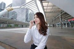 Tir grand-angulaire de la jeune femme asiatique gaie parlant au téléphone au fond extérieur de bureau Image libre de droits