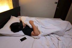 Tir grand-angulaire du sommeil confortable de jeune homme asiatique avec le masque sur le lit dans la chambre à coucher la nuit Photos stock