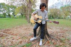 Tir grand-angulaire Homme de guitariste avec des écouteurs tenant et jouant la guitare acoustique en parc extérieur Photographie stock libre de droits