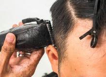 Tir haut étroit de l'homme obtenant la coupe de cheveux à la mode Client masculin de portion de styliste en coiffure, faisant la  image stock