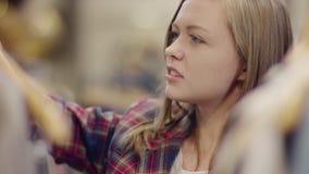 Tir haut étroit de la belle femme déçue adulte recherchant une robe intéressante sur un support dans un magasin d'habillement clips vidéos