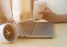 Tir haut étroit de main qui soulèvent la tasse de café rechargeable blanche temps de travail avec l'ordinateur portable et l'horl images stock