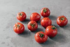 Tir haut étroit des tomates savoureuses rouges d'héritage avec les feuilles vertes et les gouttelettes d'eau moissonnées du jardi image libre de droits
