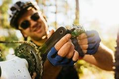 Tir haut étroit jeune de cavalier concentré et de sourire dans le casque, les verres et les gants se reposant devant sa bicyclett photographie stock