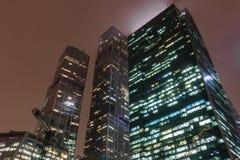 Tir horizontal de hauts bâtiments en verre de grande ville de forme différente, avec les fenêtres allumées la nuit, sur le ciel b photo libre de droits