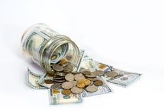 Tir horizontal des pièces de monnaie débordant le pot de pièce de monnaie Photographie stock