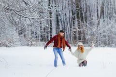 Tir intégral des couples affectueux heureux tenant des mains et le fonctionnement le long de la forêt neigeuse la belle tête roug Photographie stock libre de droits