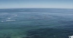 Tir large aérien parfait d'une plage de Malibu la Californie avec des vagues d'eau blanche se brisant sur le sable d'un point de  banque de vidéos
