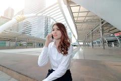 Tir large d'ange de la jeune femme asiatique attirante d'affaires s'asseyant sur l'escalier et parlant au téléphone au fond de vi Image stock