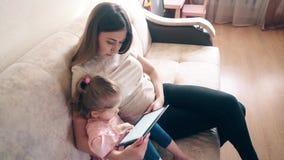 Tir latéral courbe : La jeune mère et la fille douce s'asseyent sur le divan et s'exercent utilisant le comprimé banque de vidéos