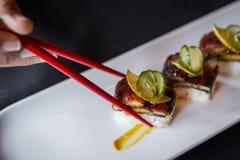 Tir latéral des sushi pris avec les baguettes rouges Image libre de droits