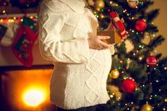 Tir modifié la tonalité de femme enceinte posant avec le boîte-cadeau de Noël Photographie stock