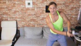 Tir moyen d'un homme dansant au jeu vidéo dans un arrangement à la maison 4k, mouvement lent banque de vidéos